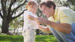 stock-footage-loving-young-caucasian-father-enjoying-visit-outdoors-park-playing-with-smiling-toddler-son-slow