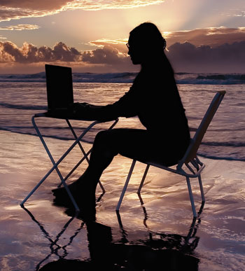 The Writer Next Door-on-beach-with-laptop